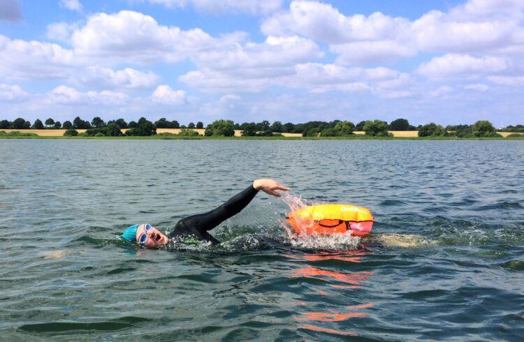 Swimmer swims with Swimmer Swimming Bouy