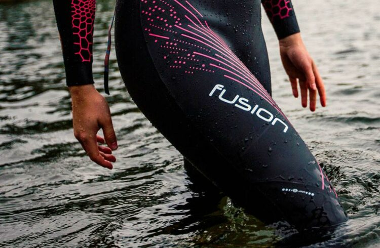 A woman entering water in blueseventy fusion wetsuit